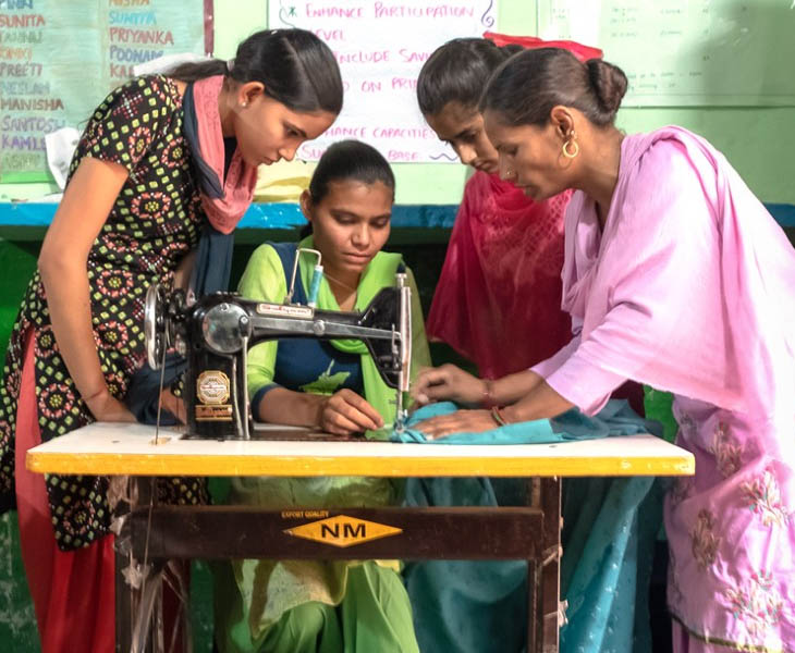 Three women stand with woman at sewing machine